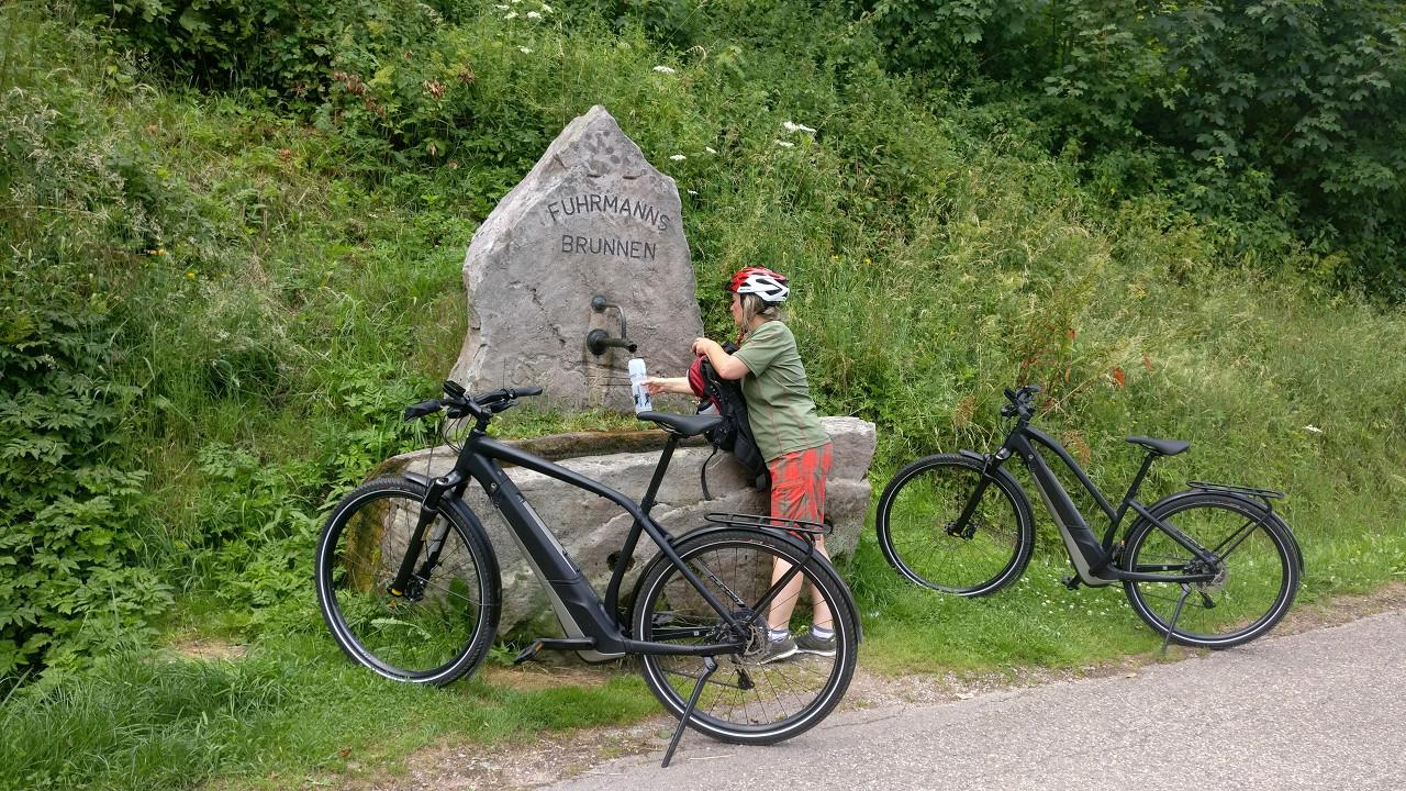 E-Bikerin füllt ihre Wasserflasche am Brunnen auf